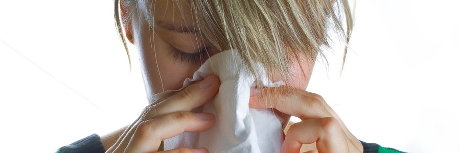 Allergy! A woman holds a white tissue to her nose. Her eyes are closed, but she is not sneezing.